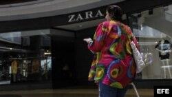 Una mujer camina frente a una de las cerradas tiendas de la franquicia que comercializa la marca española Zara en Venezuela.