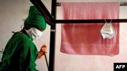 Un trabajador limpia la habitación en un centro de aislamiento para pacientes de COVID-19 en La Habana. (YAMIL LAGE / AFP)