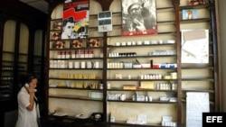 Una dependienta habla por teléfono frente a un estante de una Farmacia.