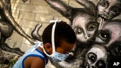 """Un niño juega junto a un mural del artista Yulier P. titulado """"Marcha Hacia la Oscuridad"""", en La Habana. (AP/Ramon Espinosa)"""