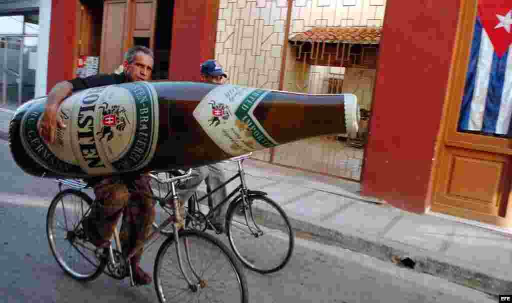 Un hombre se traslada en bicicleta con una botella de cerveza inflable, en la provincia de Camaguey, Cuba.
