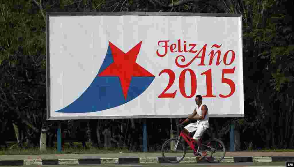 Un hombre pasa en bicicleta frente a una valla alusiva al nuevo año el miércoles 31 de diciembre de 2014, en La Habana (Cuba).
