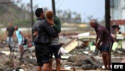 Cubanos buscan objetos entre los escombros dejadps por Matthew.