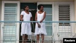 Mujeres observan desde una balcón una marcha contra la homofobia en La Habana. REUTERS/Alexandre Meneghini
