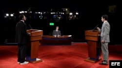 Dos personas en los atriles del escenario simulan el debate presidencial entre el republicano Mitt Romney (d) y el demócrata Barack Obama (i) en la Universidad de Denver, Colorado.