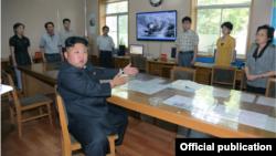 El líder máximo diserta sentado sobre meteorología mientras los meteorólogos escuchan, de pie.