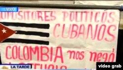 Los cubanos Rafael Hernández y Yunieski Borges desplegaron este cartel en la Plaza Bolívar de Bogotá