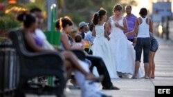 Una joven es ayudada por sus familiares a acomodar su vestido de quinceañera antes de posar para el fotógrafo en la Habana.