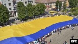 Varios ciudadanos sostienen la bandera de Ucrania, considerada la más grande del mundo, con 60 metros de largo por 40 metros de ancho, en la ciudad de Chernivtsi.
