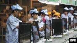 Varias operarias chinas trabajan en una línea de montaje de televisores en una fábrica de Shenyang, en la provincia de Liaoning (China) hoy, lunes 27 de agosto de 2012. Firmas industriales chinas registraron caídas en sus beneficios por cuarto mes consecu