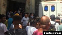 Vecinos se reúnen alrededor de la ambulancia en el lugar del derrumbe. (Foto tomada del Facebook de Isladaris Benítez)