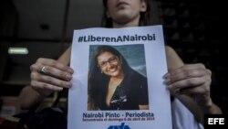 Una periodista muestra un afiche que exige la liberación de la jefa de Corresponsalías del canal venezolano de televisión Globovisión, Nairobi Pinto,