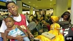 ARCHIVO. Una joven familia de emigrados cubanos esperan noticias sobre su vuelo hacia Cuba.