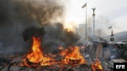 Manifestantes permanecen tras pilas de neumáticos incendiados durante las protestas violentas en el centro de Kiev (Ucrania), hoy, miércoles 19 de febrero de 2014.