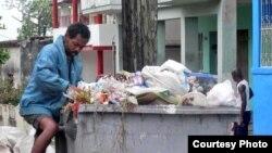 """Pobreza rampante: un """"buzo"""" registra la basura en busca de algo que vender (foto Iván Libre)"""