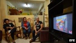 Una familia observa en la televisión la noticia de la muerte del presidente venezolano. Los problemas de salud de Chávez han generado en los cubanos preocupación por una nueva recaída económica en la isla.