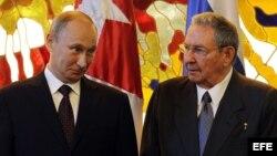Raúl Castro (d) y su homólogo de Rusia Vladimir Putin (i) hablan antes de hacer declaraciones a la prensa.