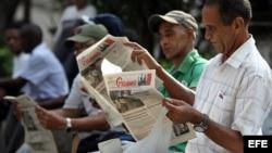 Varios hombres leen el diario oficial Granma en La Habana (Cuba).