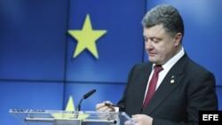 Petro Poroshenko, mira su bolígrafo mientras da una rueda de prensa en el ámbito de la segunda jornada de la cumbre de la Unión Europea en Bruselas (Bélgica).