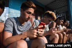 Jóvenes cubanos se conectan a internet en un punto WiFi de La Habana.