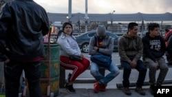 Migrantes esperan a la entrada del Puente Internacional Paso del Norte, en Ciudad Juárez.