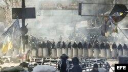 Varios manifestantes permanecen tras una barricada ante un cordón policial en Kiev (Ucrania) el viernes 31 de enero de 2014.