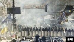 Varios manifestantes permanecen tras una barricada ante un cordón policial en Kiev (Ucrania). Archivo.