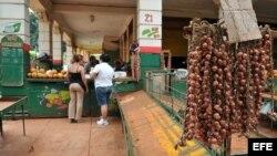 ARCHIVO. Dos mujeres compran cebollas en un agromercado en La Habana.