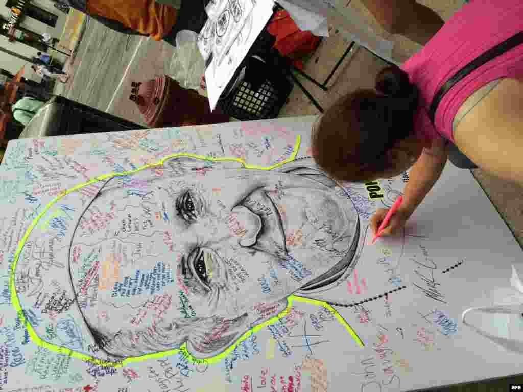 Una mujer firma sobre una imagen del papa Francisco en Filadelfia.