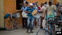 Cubanos hacen colas fuera de las tiendas para comprar pan en San José de las Lajas (Yamil Lage / AFP).