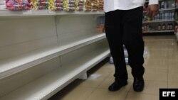 Un hombre camina por un pasillo de supermercado frente a estanterías desabastecidas hoy, viernes 1 de febrero de 2013, en Caracas (Venezuela).