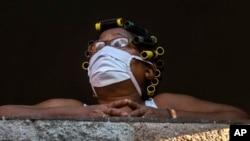 Una mujer mira por su ventana durante la pandemia del coronavirus en Cuba. AP Photo / Ramon Espinosa