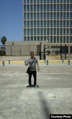 El activista del MCL, Michel Camacho, hace la señal de la libertad frente a la embajada de Estados Unidos en La Habana, 20 de julio 2015.
