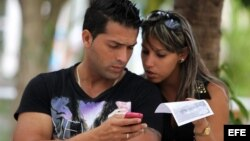 Dos jóvenes usan un teléfono móvil hoy, miércoles 9 de abril de 2014, en La Habana (Cuba)