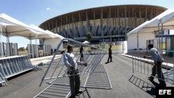 """Trabajadores brasileños instalan unas vallas de seguridad delante del Estadio Nacional """"Mane Garrincha""""."""