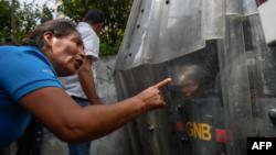 Mujer venezolana, desarmada, reprocha a la guardia madurista preparada para reprimir