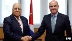 El ministro español de Economía y Competitividad en funciones, Luis de Guindos (d), y el vicepresidente del Consejo de Ministros de Cuba, Ricardo Cabrisas Ruiz (i), se saludan durante la firma de los acuerdos para reestructurar la deuda cubana con España