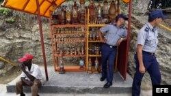 Dos policías observan desde una caseta artesanal, en el poblado El Cobre, Santiago de Cuba.