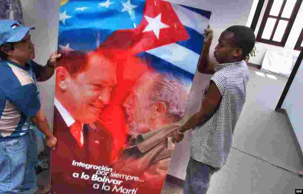 Dos obreros trasladan un cristal con la imagen de Hugo Chávez y Fidel Castro.