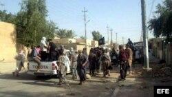 Rebeldes permanecen en una calle de Tikrit, norte de Irak, hoy miércoles 11 de junio de 2014. La ofensiva sobre el norte de Irak de los insurgentes suníes, encabezados por el Estado Islámico de Irak y el Levante (EIIL), cobró hoy un nuevo impulso con su e
