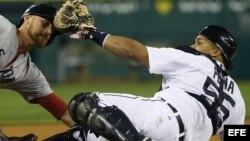 El receptor de Tigres Brayan Peña (d) choca con el árbitro de tercera base Rob Drake (i).