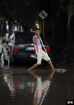 Un joven cruza una calle inundada en La Habana. Archivo.