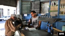 Un bodeguero vende productos racionados a un cliente en La Habana.