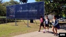 Jóvenes caminan frente a un cartel de la II Cumbre de la Celac.