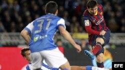Leo Messi golpea el balón ante los defensores de la Real Sociedad
