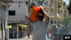 Un residente de La Habana carga una bolsa con alimentos el 17 de abril del 2020.