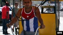 Un bicitaxista usa una camiseta con la bandera cubana por una calle de La Habana.