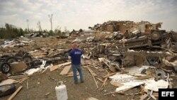 Unos hombres recuperan pertenencias en medio de los escombros en Mayflower R.V. Park tras el paso de un tornado que azotó este, 27 de abril, en Mayflower, Arkansas (EEUU).