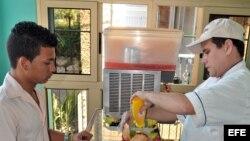 """Un joven es atendido en la cafetería de un trabajador """"cuentapropista"""" en La Habana (Cuba)."""