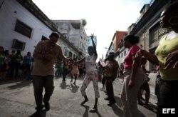 """Personas afines al Gobierno cubano bailam y mantienen rodeada la sede de las Damas de Blanco y les impide asistir a la iglesia para celebrar el día de la virgen de """"La Merced"""", patrona de los presos."""